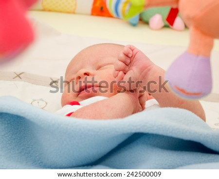 Newborn boy is sleeping in his bed under a blue blanket among bright toys - stock photo