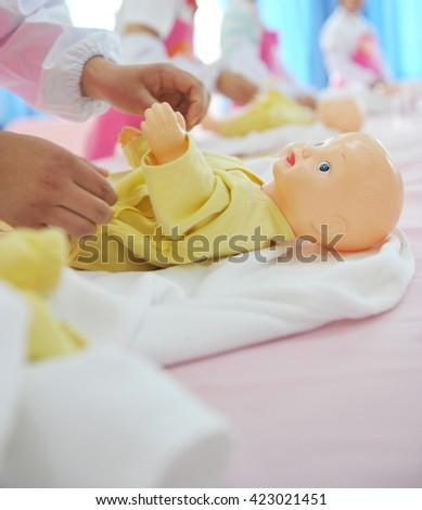newborn care exercise on infant dummy. - stock photo
