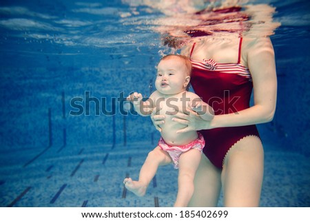 newborn child swims underwater - stock photo