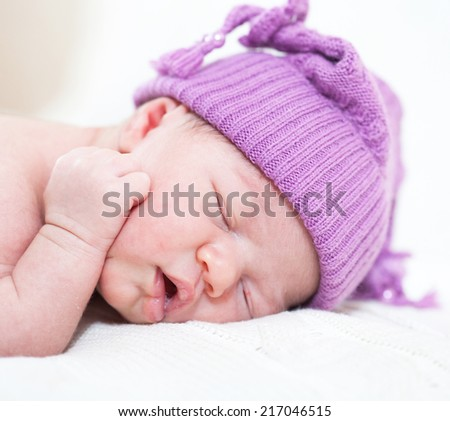 newborn child with a ridiculous violet hat sleeps - stock photo