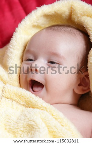 Newborn - close-up focus baby boy with yelow blanket with  smile - stock photo