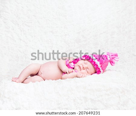 Newborn cute baby sleep in a pink knitted hat