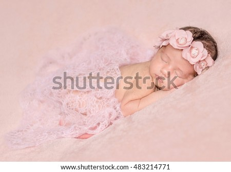 newborn cute girl sleeping on a pink background