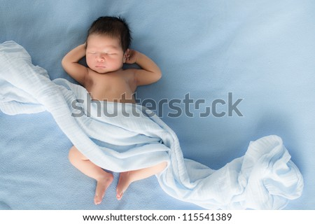 Newborn 4 day old baby boy lying on his back relaxing under a blue wrap cloth - stock photo