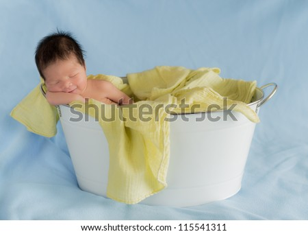 Newborn 4 day old baby sleeps with a knowing smile in a white washtub - stock photo