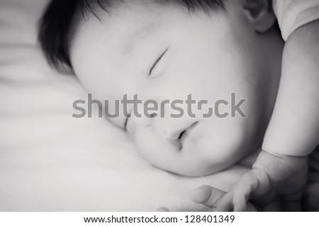 Newborn face and dark hair sleeping peacefully - stock photo