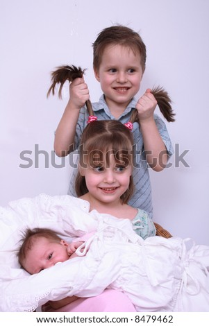 newborn girl and her brother and sister - stock photo