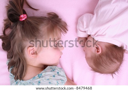 newborn girl and her sister - stock photo