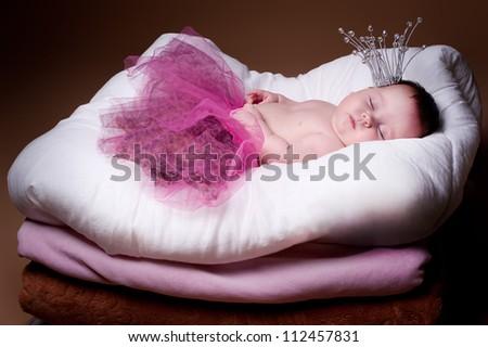newborn girl in a princess costume. sleeps. - stock photo