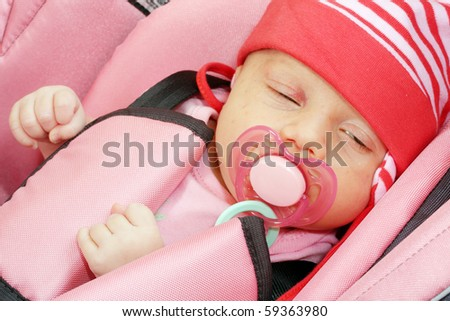 Newborn girl in child safety seat. - stock photo