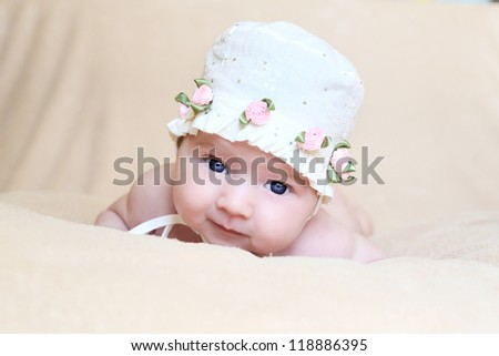 newborn girl in white cap with flowers