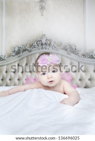 newborn girl on a bed with a beautiful headboard in the background - stock photo