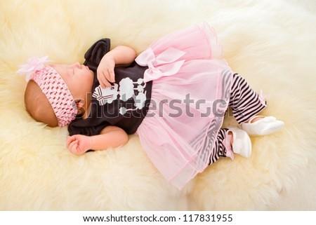 Newborn girl sleeping in cute dress - stock photo