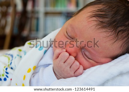 Newborn girl sleeping on her mother shoulder - stock photo