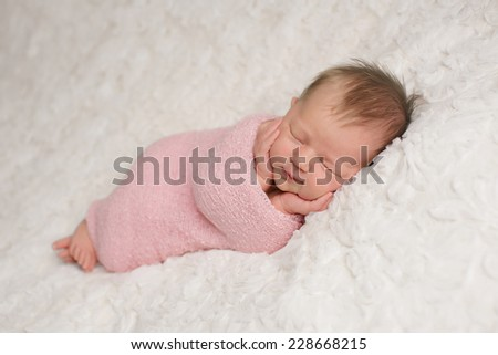Newborn girl swaddled in pink wrap with hands on her cheeks - stock photo