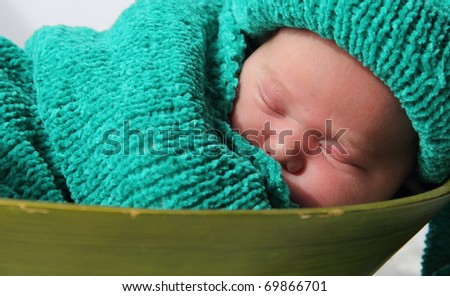 newborn in a knitted cocoon and hat - stock photo