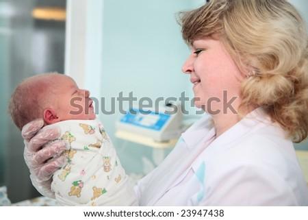 newborn in childbearing center and doctor - stock photo