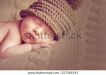 Newborn in hat blankets on the brown - stock photo