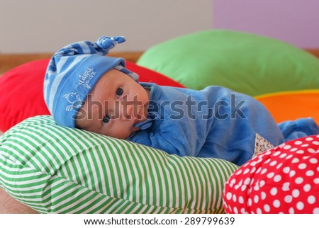 Newborn in nursery lying on colorful pillow - stock photo
