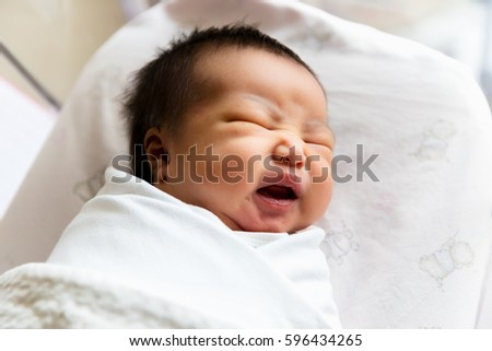 Newborn infant asleep in the blanket in delivery room, 2 days after birth