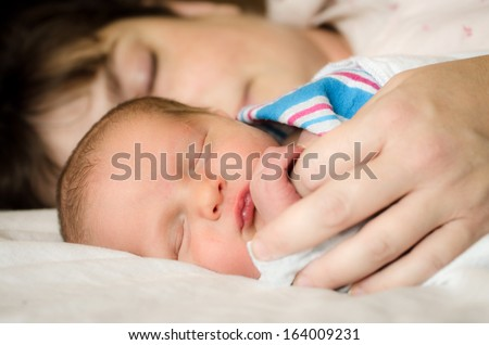 Newborn infant child resting next to mother after delivery at hospital - stock photo