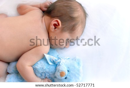 Newborn infant cuddles his blue teddy and sleeps in a dreamland of white.  Blank space for personalization. - stock photo