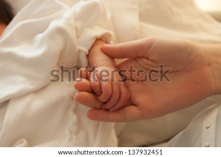 Newborn infant toddler baby hands a few days old holding mothers hand