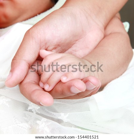 Newborn infant toddler baby hands a few days old holding mothers hand.