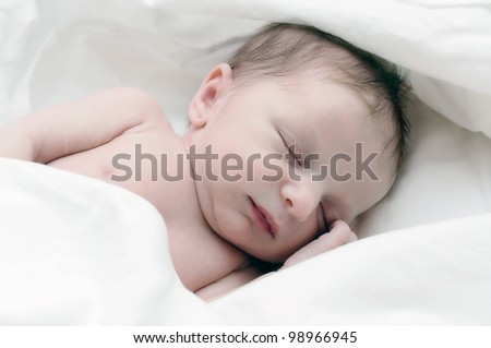 Newborn infant wrapped in white blanket. - stock photo