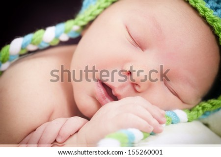Newborn is asleep in a cute hat - stock photo