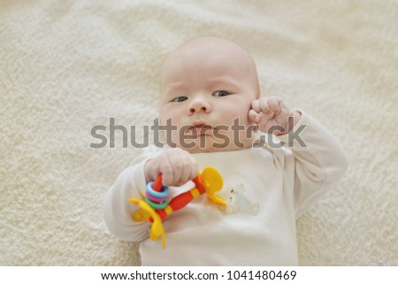 newborn little  baby laying  with toy on the bed
