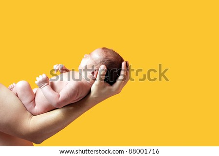 newborn on hand father isolated on yellow background - stock photo