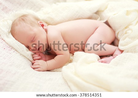 Newborn sleeping baby girl on a white blanket