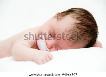 Newborn sleeping child on white blanket - stock photo