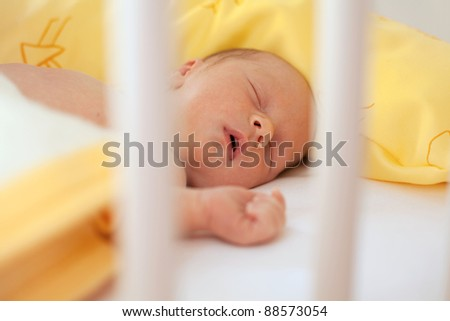 newborn sleeping in a crib - stock photo