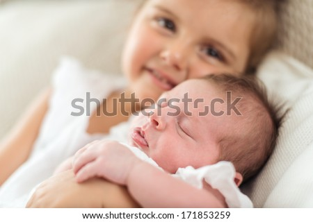 Newborn sleeping in her sister's arms - stock photo