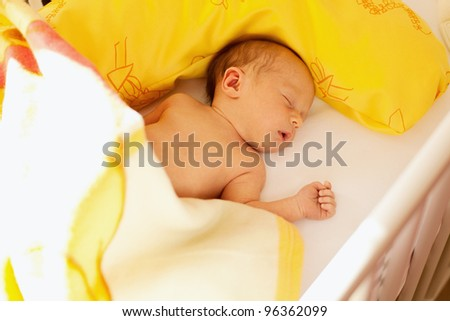 newborn sleeping in his crib