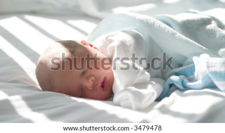 Newborn sleeping in hospital bed awash with light through the blinds