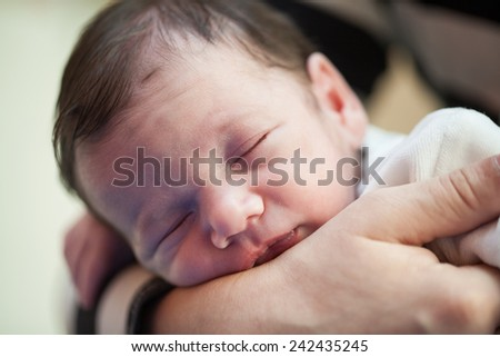 Newborn  sleeping in mother's hands