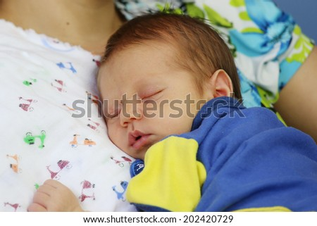 Newborn sleeping in the arms of his mother - stock photo