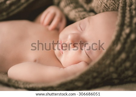 Newborn sleeping peacefully 11 days wrapped in a blanket