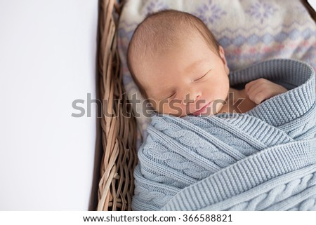 newborn sleeps in a basket in a knitted shawl - stock photo