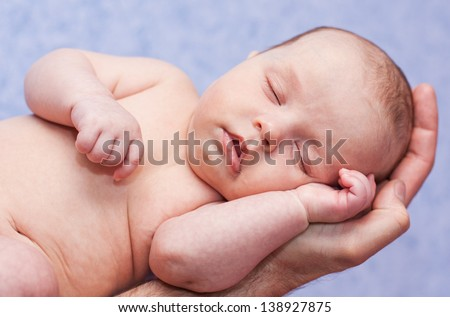 newborn sleeps on a hand on a blue background - stock photo