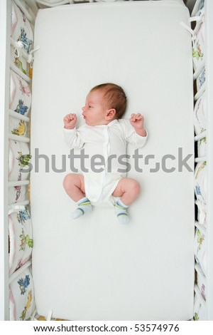 Newborn small boy sleeping in his big bed - stock photo