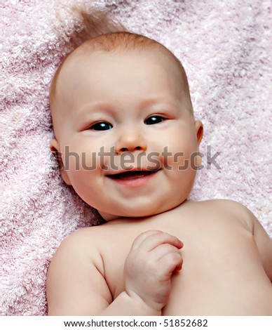 Newborn smiling baby on the pink blanket