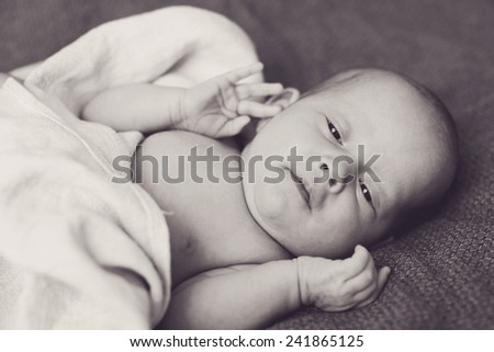 newborn tiny baby lying on the bed - stock photo