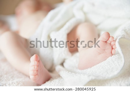 newborn tiny baby lying on the bed with blanket. Focus on feet, - stock photo