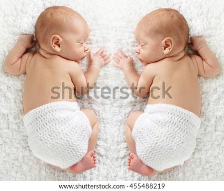 Newborn twin babies, sleeping on a white blanket.  - stock photo