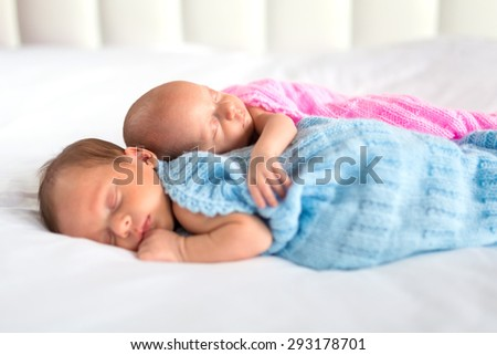 Newborn twins sleeping in cuddle together - stock photo
