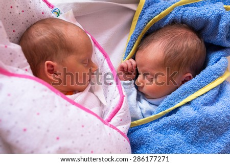 Newborn twins sleeping together - stock photo